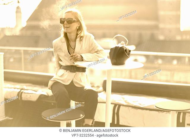 fashionable blogger woman taking break outdoors at balcony in city Munich, Bavaria, Germany