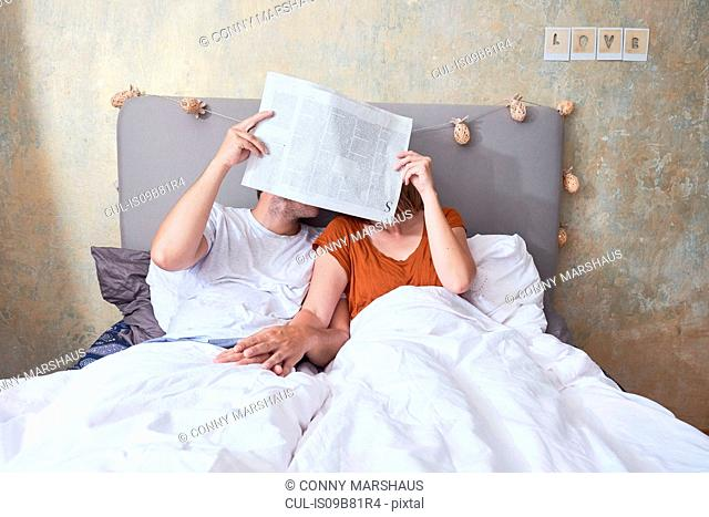 Couple in bed, holding hands, holding newspaper in front of faces