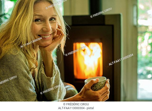 Mature woman relaxing with coffee at home, portrait