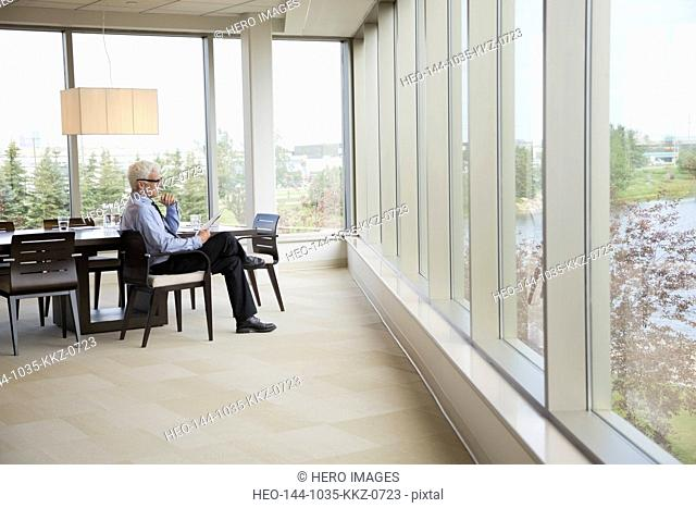 Businessman reviewing documents in boardroom