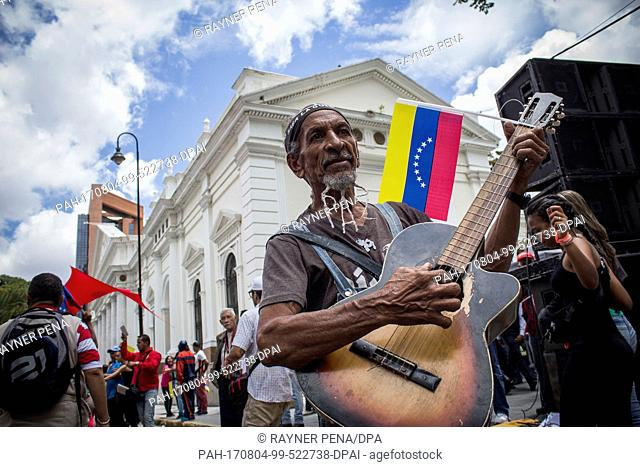 """A government supporter celebrates the start of a constitutional assembly with a guitar, the word """"""""peace"""""""" on his beard and a Venezuelan flag in Caracas"""