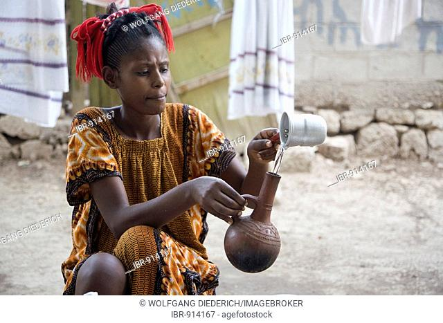 Young woman, 20-25 years old, pouring coffee into a coffee pot, Massawa, Eritrea, Africa