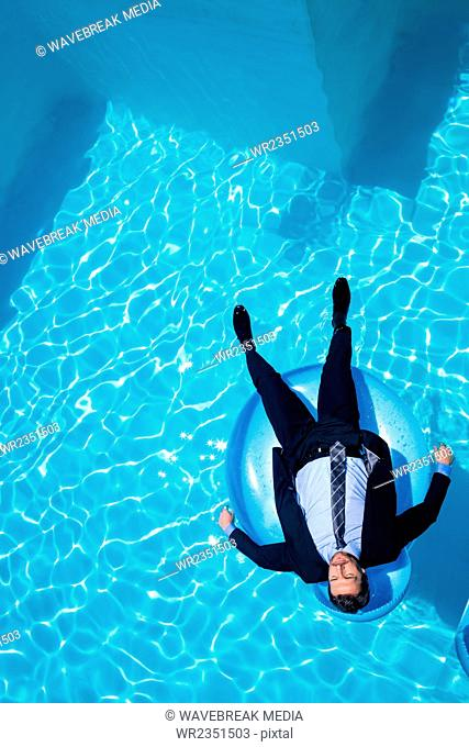 Businessman relaxing on inflatable