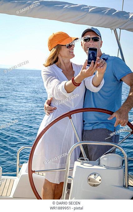 Mature couple sailing together, taking pictures, Adriatic Sea, Croatia