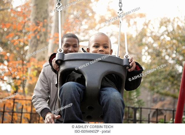 Father pushing toddler son on park swing