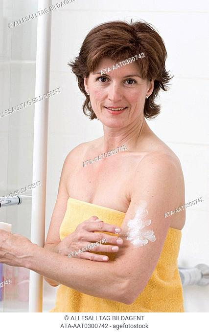 Midage woman putting some lotion on her upper arm