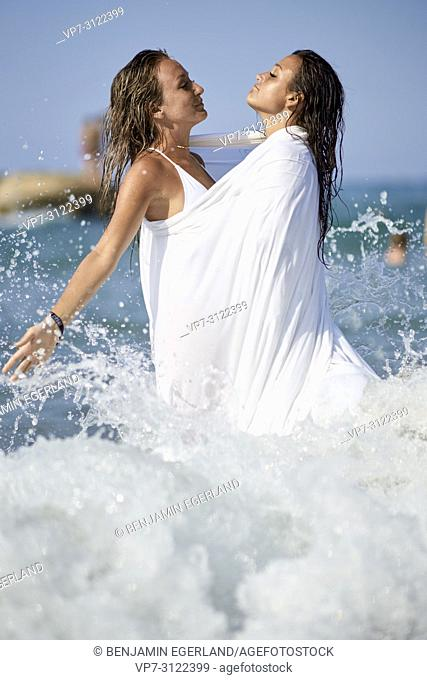 two sensual women shrouded in white blanket sheet, in sea, best friends, friendship goals, holidays, adventure, water, splashes