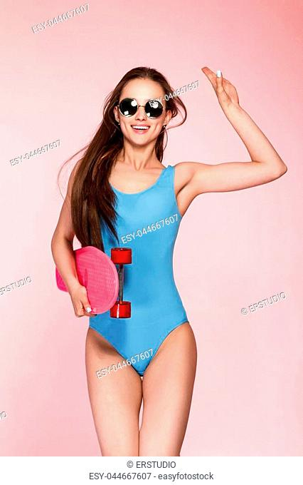 beautiful woman in blue bodysuit holding skateboard on pink background