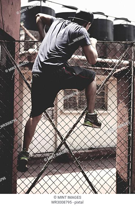 Young man climbing over a chain link fence in an urban environment