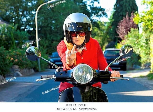 Crotchety old lady on a scooter making a rude gesture of dismissal with her finger as she sits looking over the handbars with a disdainful expression