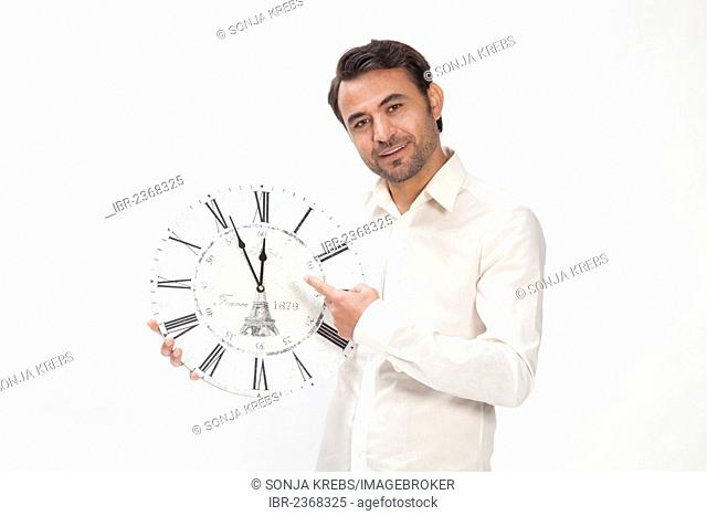 Man holding a clock at eleven fifty-five, almost high noon