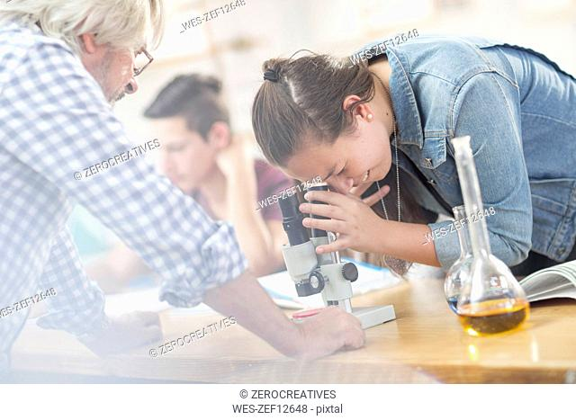 Science student with teacher in class looking through microscope