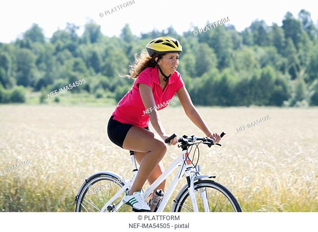 A woman riding a bike in the countryside, Sweden