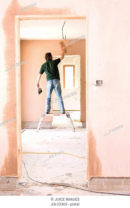 Man on step stool plastering wall in house under construction