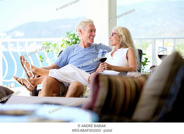 Happy senior couple with glass of red wine in home by the sea