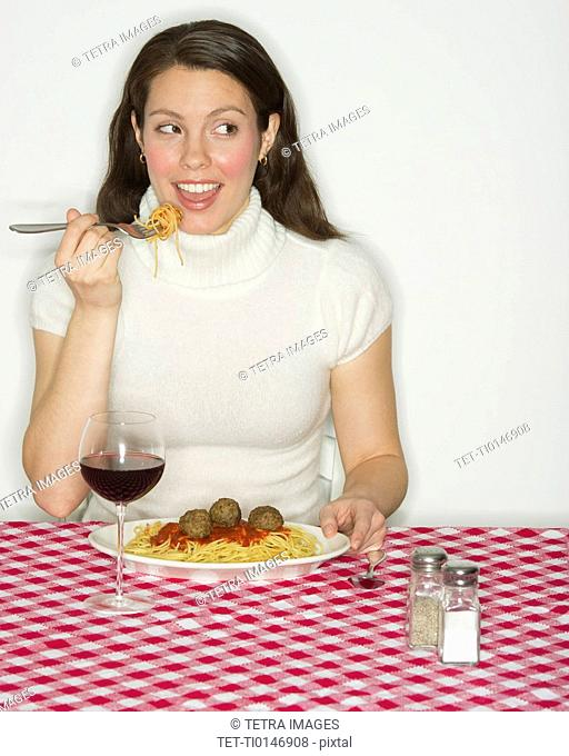 Portrait of woman eating spaghetti with meatballs