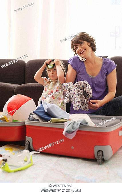 Germany, Leipzig, Mother and daughter 4-5 packing suitcase, mother using phone