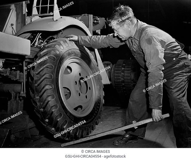Worker Mounting a Wheel on Army's Half-Track Scout Car at Factory Converted to War Production, White Motor Company, Cleveland, Ohio, USA, Alfred T