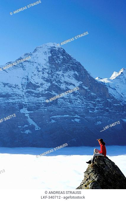 Woman sitting on rock and looking towards north face of Eiger above sea of fog, Bussalp, Grindelwald, UNESCO World Heritage Site Swiss Alps Jungfrau - Aletsch