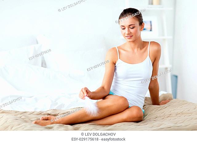 people, beauty, depilation, epilation and bodycare concept - beautiful woman sitting on bed and touching bare legs with feather at home bedroom