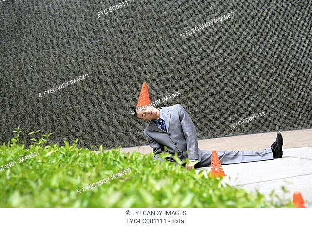 Young businessman doing split outdoors with traffic cone on head