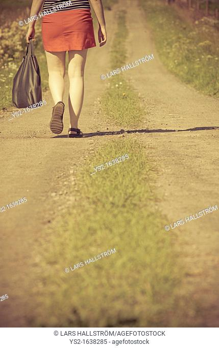 Woman walking on a dirt road