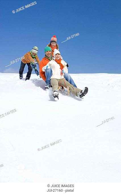 Children pushing parents downhill on sled on ski slope