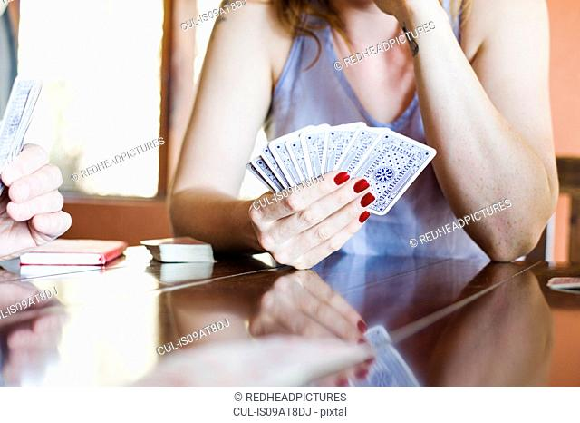 Cropped shot of young woman playing cards