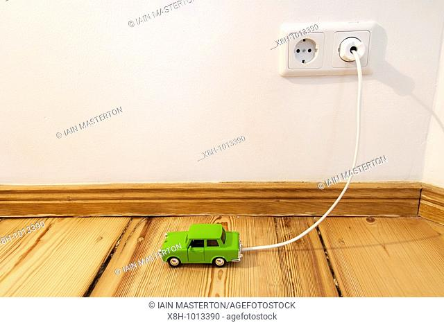 Concept of toy electric car being recharged by plug-in connection to electric supply in the home