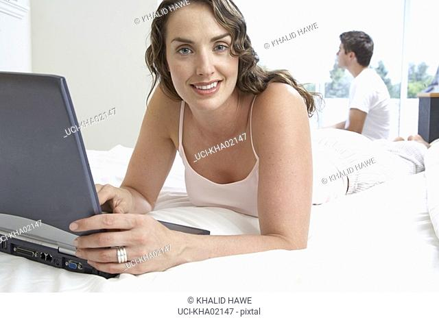 Young woman using laptop in bed