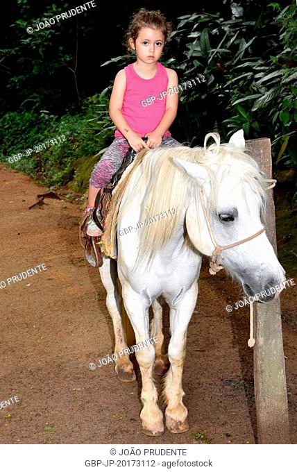 Three year old girl preparing for pony ride in old farm adapted for rural tourism, Itu, São Paulo, Brazil, 01.2017