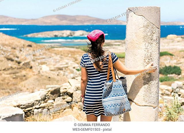 Greece, Mykonos, Delos, tourist at archaeological site enjoying the view