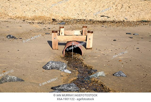 Drainage pipe emptying water onto sandy beach, Felixstowe, Suffolk, England