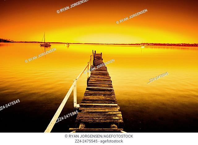 Collapsing old wooden pier with missing wooden planks and hand rails landscaped before a bright ocean sunset with colorful tints of orange and yellow