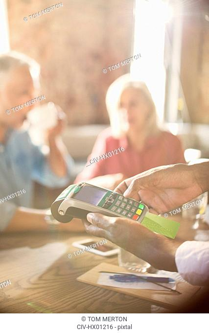 Waiter using credit card reader at restaurant table