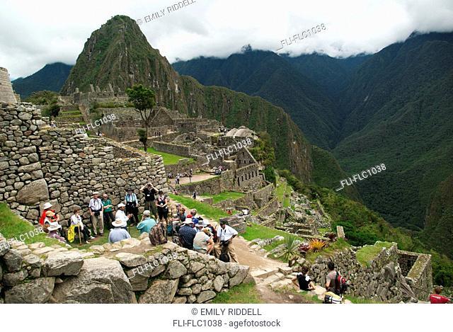 Tourists resting in ruins, Machu Picchu, Peru