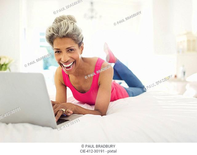 Portrait laughing mature woman using laptop on bed