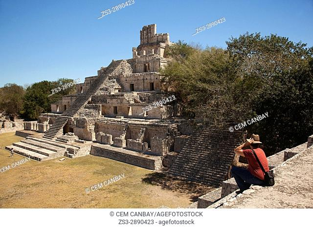 Visitor sitting on the stairs in front of the Edificio de los Cinco Pisos building at Gran Acropolis in Edzna Mayan Archeological site, Campeche State, Mexico