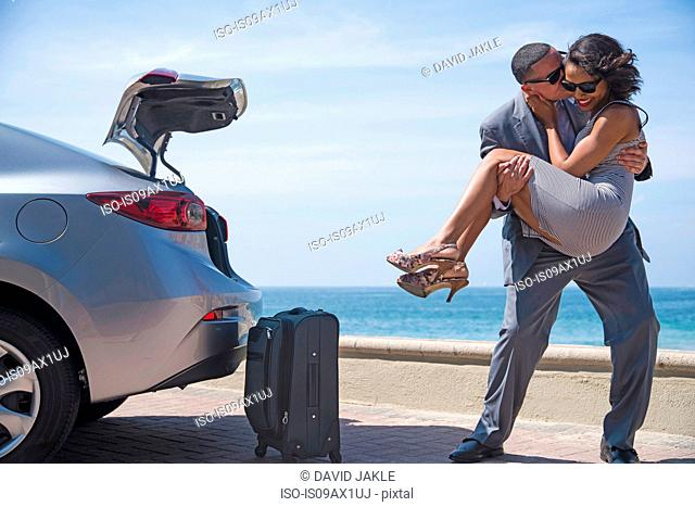 Man kissing woman in arms beside luggage on beach