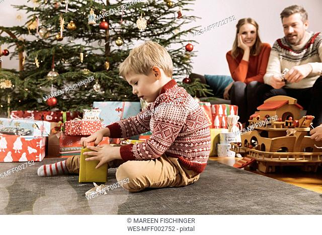 Little boy opening Christmas gift with parents watching in background