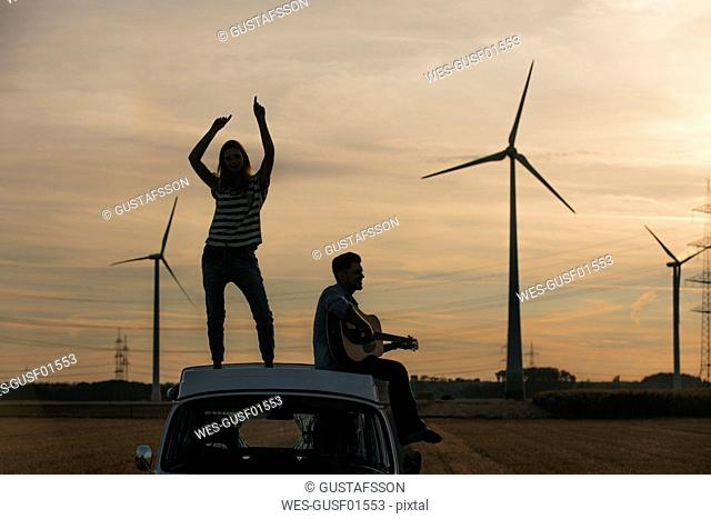 Happy couple with guitar on roof of a camper van in rural landscape at dusk