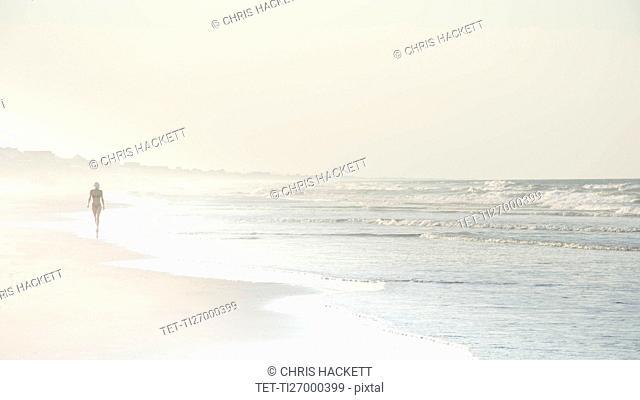 USA, North Carolina, Woman walking on empty beach