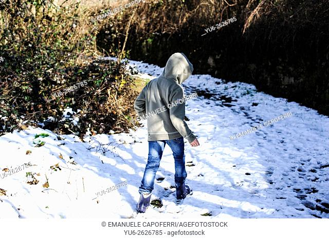 Boy walking along a path with snow