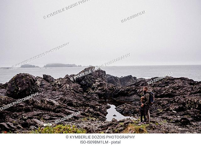 Father and child walking on rocks, Tofino, Canada