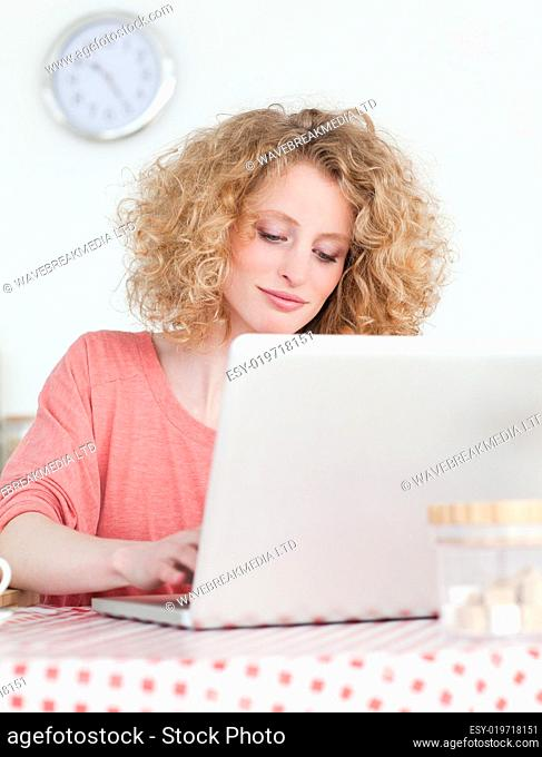Beautiful blonde woman relaxing with her laptop while sitting in
