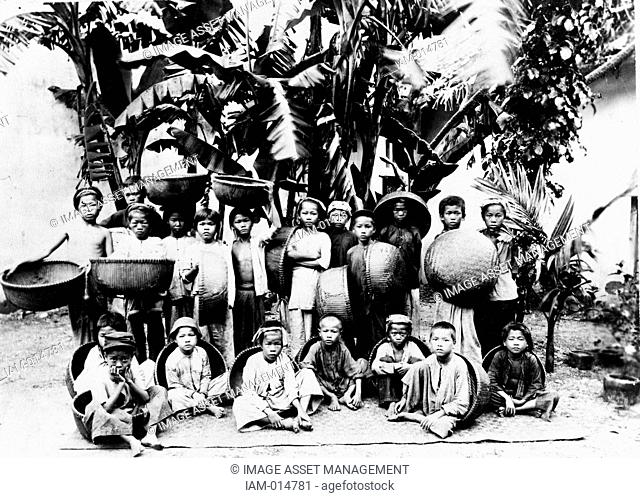 Children with locally made baskets posed under a palm tree, Saigon South Vietnam, c1900. Saigon was the capital and commercial centre of French colonialism in...