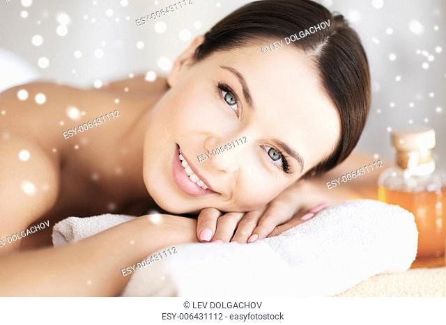 beauty, health, people and spa concept - beautiful young woman in spa salon lying on the massage desk