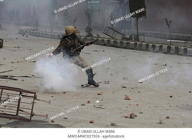 An Indian policeman throws a tear smoke shell towards students during a protest againest the recent killings in kashmir,outside a collage in Srinagar on April...