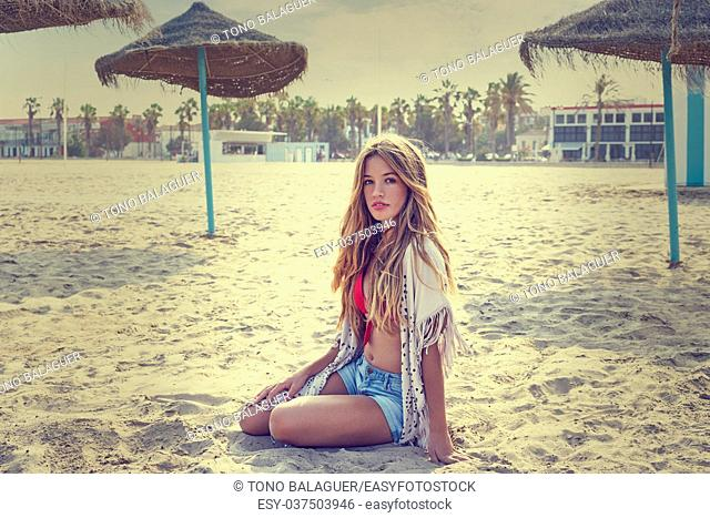 Blond teen girl sit on the beach sand near thatch umbrellas