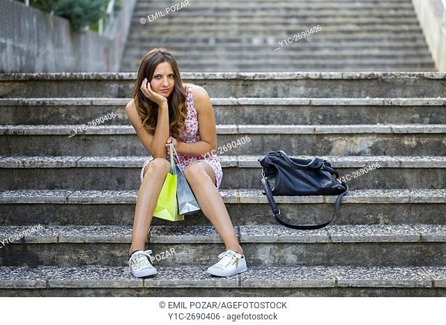 Young woman shopper tired after shopping